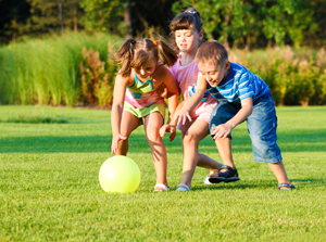 kids playing with ball on summer lawn
